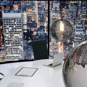 Modern office with vintage lightbulbs and city view at evening